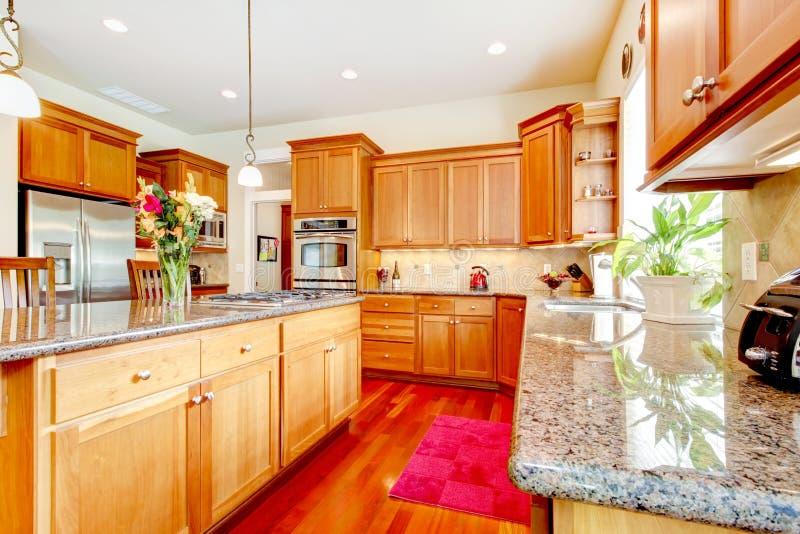 Drewniana luksusowa wielka kuchnia z czerwienią i granitem. obraz stock