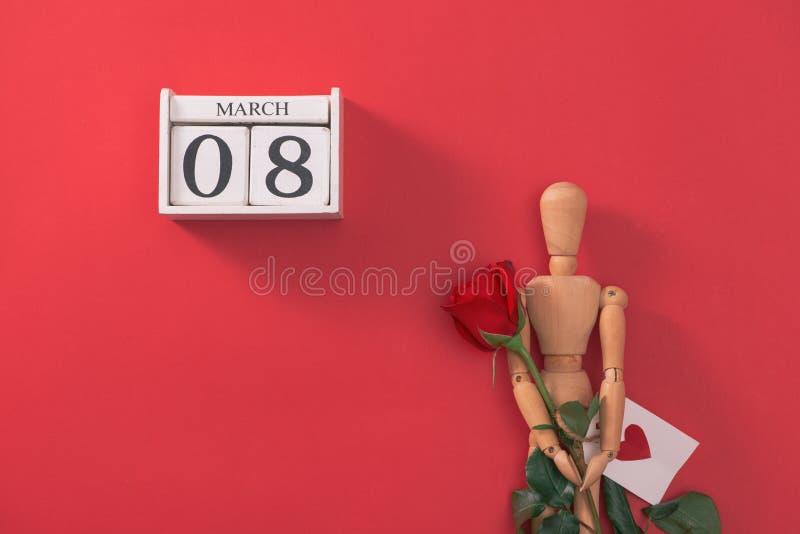 Drewniana mężczyzna postać z czerwonymi kwiatami Pojęcie dla walentynki ` s dnia obrazy royalty free