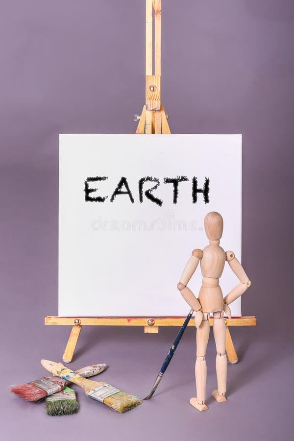 Drewniana manikin lali pozycja przed kanwą z słowo ziemią malował w czerni obrazy royalty free