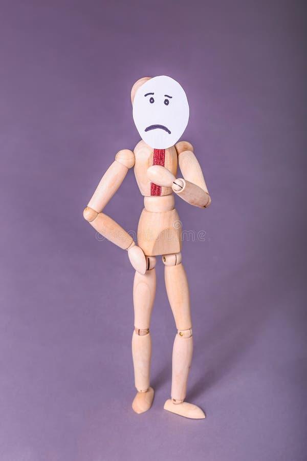 Drewniana manikin pozycja z jeden ręką na biodra jeden ręce podtrzymuje smutną twarz podpisuje jego twarz zdjęcia stock