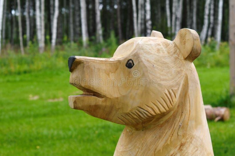 Drewniana naturalna postać niedźwiedź który ciie za drzewie od obraz stock