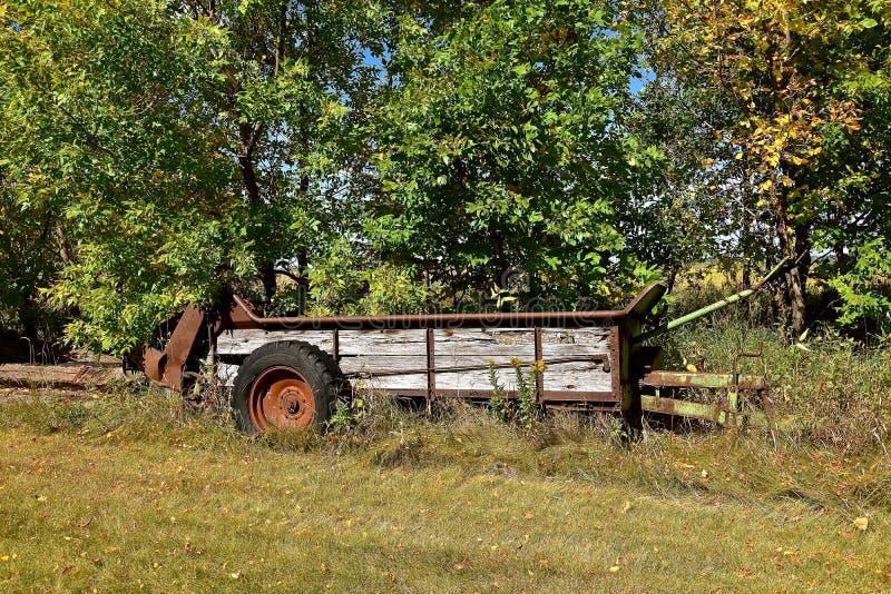 Drewniana nawóz powlekaczka opuszczał w długiej trawie fotografia stock
