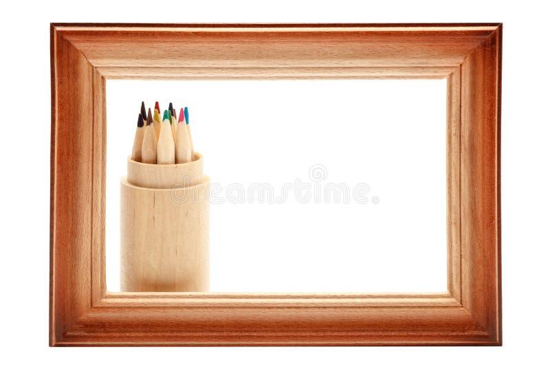 Drewniana obrazek rama i barwioni ołówki na bielu zdjęcia stock