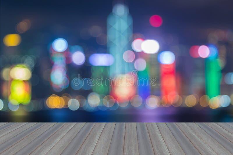 Drewniana platforma z abstrakt zamazującym bokeh Hong Kong miastem zaświeca skylin zdjęcie stock