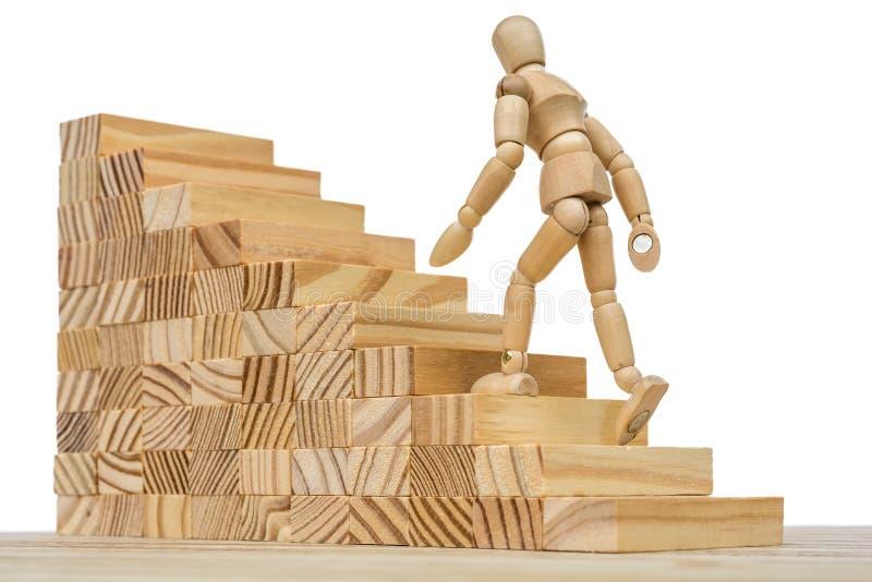 Drewniana postać biega w górę wysokich schodków jako metafora dla pracy i kariery ilustracji