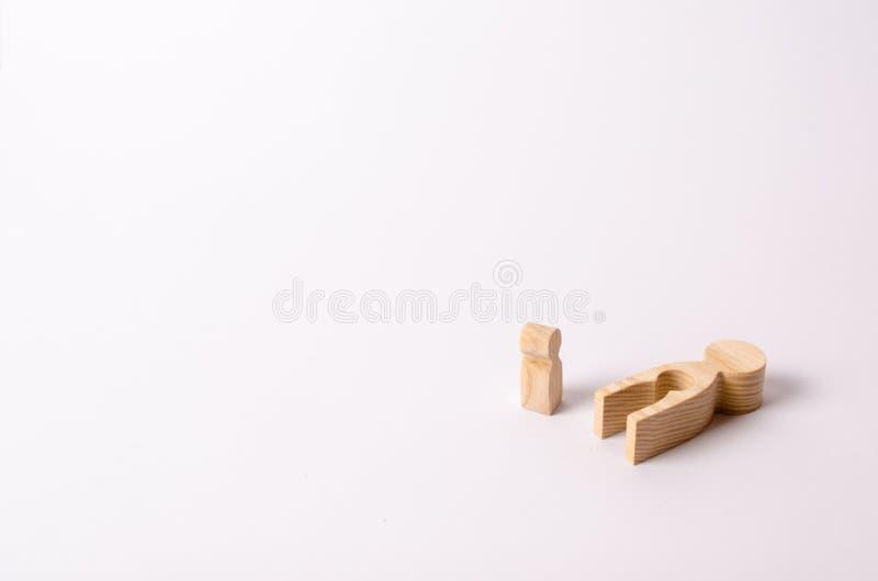 Drewniana postać dziecko stojaki obok jego matki ` s spojrzenia przy nim i lody Matka dziecko umierał obrazy stock
