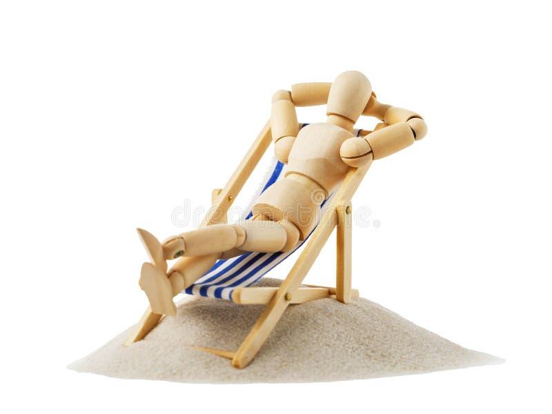 Drewniana postać w postaci mężczyzna odpoczywa na deckchair zdjęcia stock