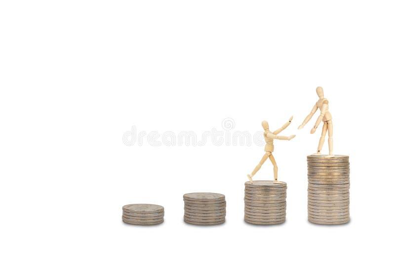 Drewniana postaci mannequin pozycja na wierzchołku brogować srebne monety i ciągnięcie inna postać iść wierzchołek fotografia stock