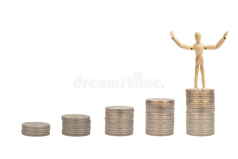 Drewniana postaci mannequin pozycja na wierzchołku brogować srebne monety odizolowywać na białym tle obrazy royalty free
