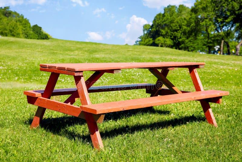 Drewniana pykniczna ławka na zielonej trawy polu w parku obraz royalty free