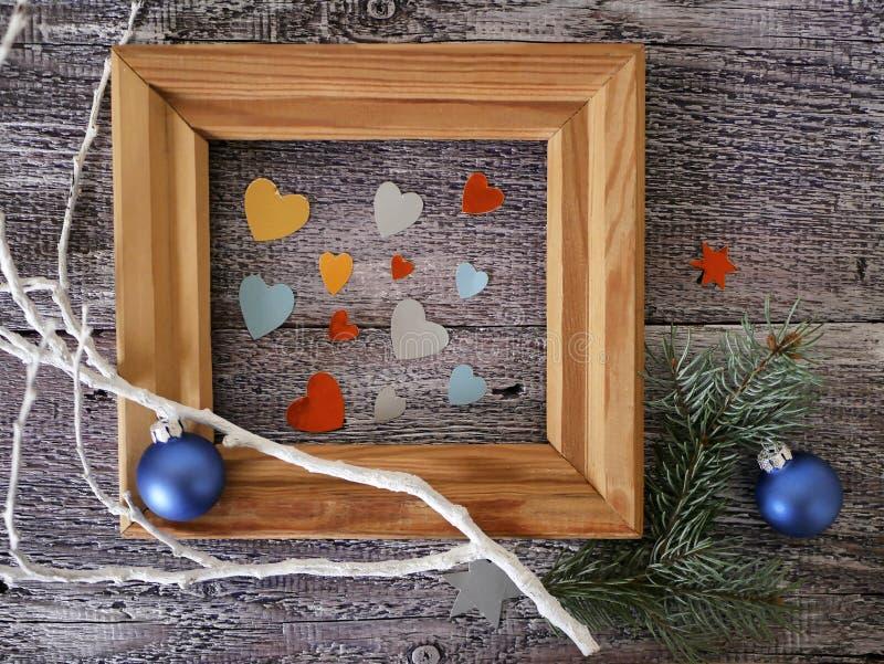 Drewniana rama z pustą przestrzenią na drewnianym szorstkim tekstury tle, sezonowy świąteczny wystrój, piłki, serca, gwiazdy, odg fotografia stock