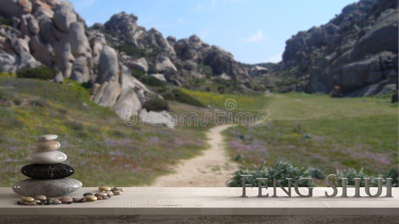 Drewniana rocznika stołu półka z otoczak równowagą i 3d pisze list robić słowa feng shui nad zamazaną zieloną doliną z granitowym obrazy royalty free