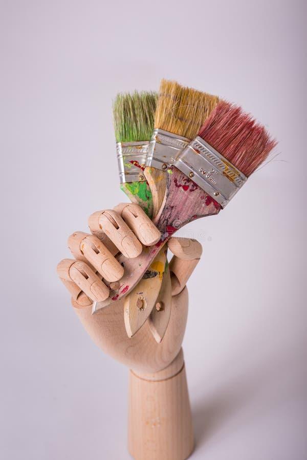Drewniana spajająca manikin ręka podtrzymuje trzy paintbrushes fotografia royalty free