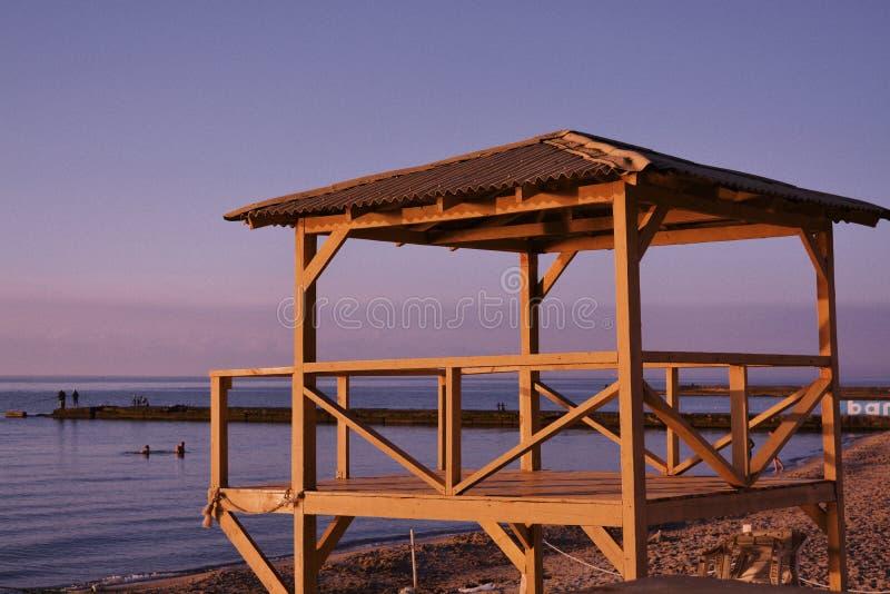 Drewniana struktura z dachową pokrywą budował na drewnianym molu z morzem i niebie w tle zdjęcie royalty free