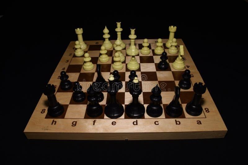 Drewniana szachowa deska i czarne bierki lubimy gemowego tło zdjęcia royalty free