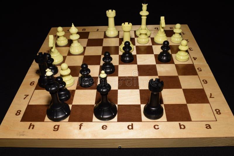 Drewniana szachowa deska i czarne bierki lubimy strategii tło obrazy royalty free