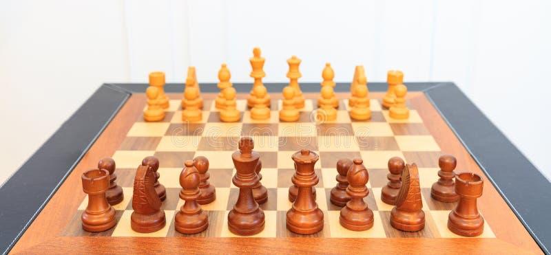 Drewniana szachowa deska z kawałkami na nim Skóry rama, zamyka w górę widoku, szczegóły, biały tło royalty ilustracja