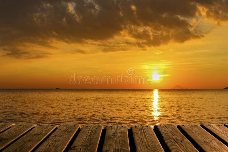 Drewniana tekstura i Piękny tło z oceanem, słońcem i chmurami przy świtem, fotografia stock