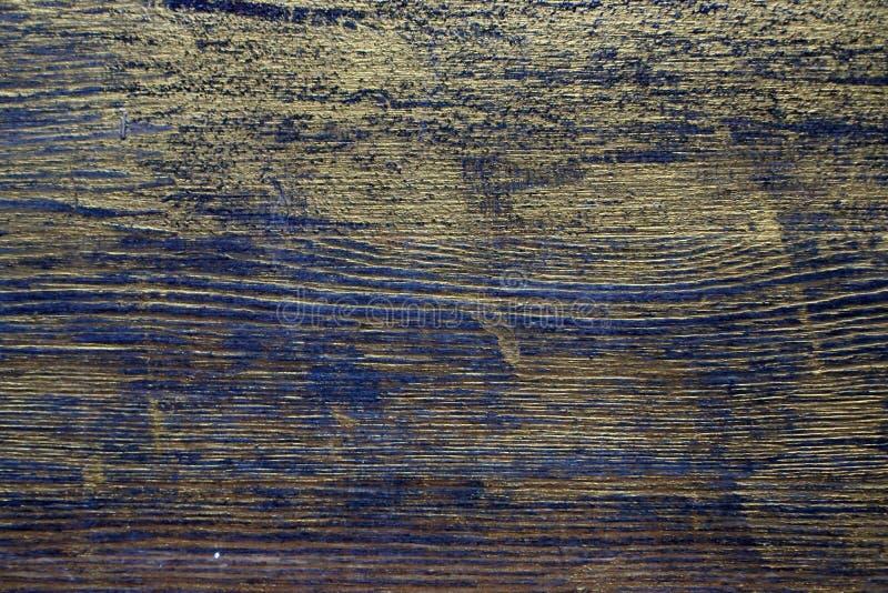 Drewniana tekstura taktująca z heban plamą i złocistą farbą fotografia royalty free