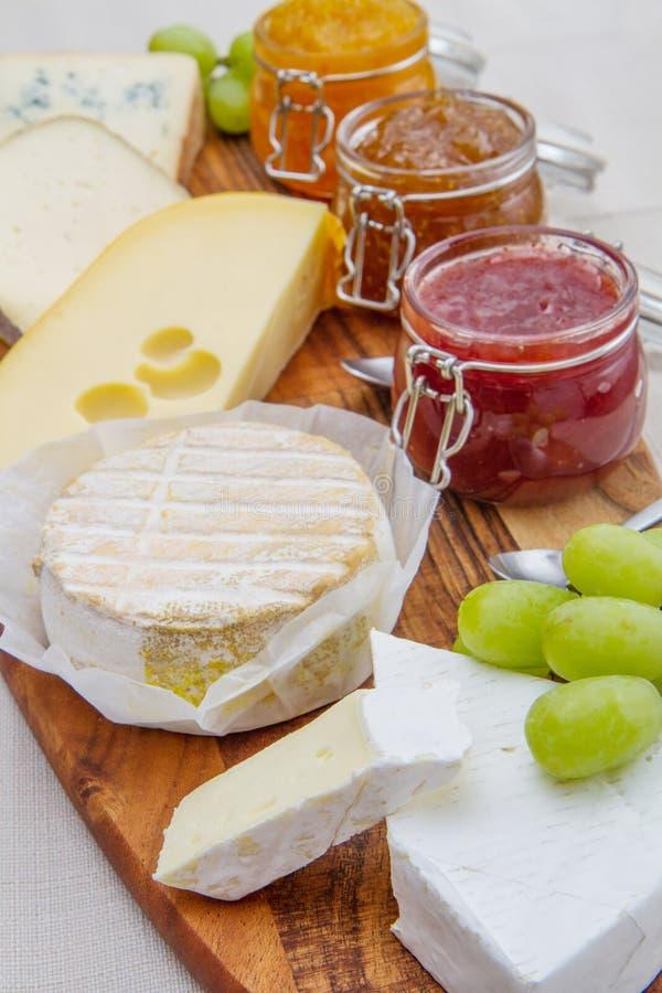 Drewniana tnąca deska z serem i dżemami obraz royalty free