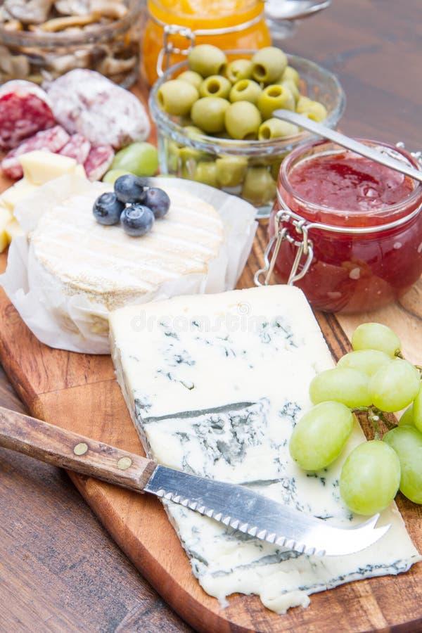 Drewniana tnąca deska z serem, zimnymi cięciami i dżemami, fotografia stock