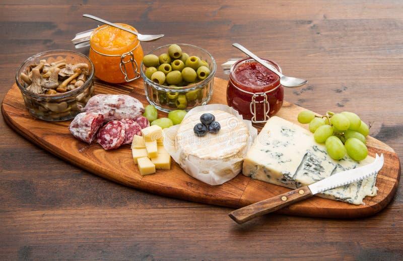 Drewniana tnąca deska z serem, zimnymi cięciami i dżemami, zdjęcie royalty free