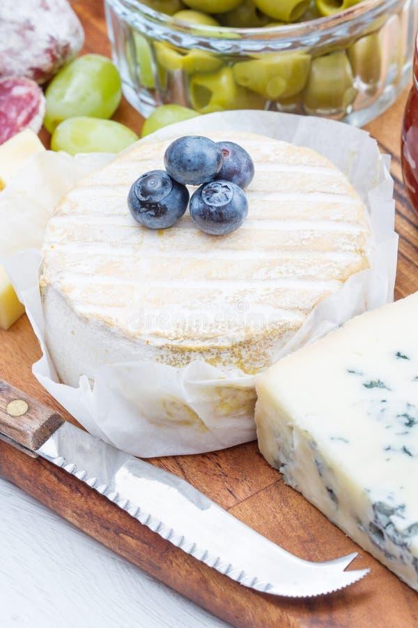 Drewniana tnąca deska z serem, zimnymi cięciami i dżemami, zdjęcia stock