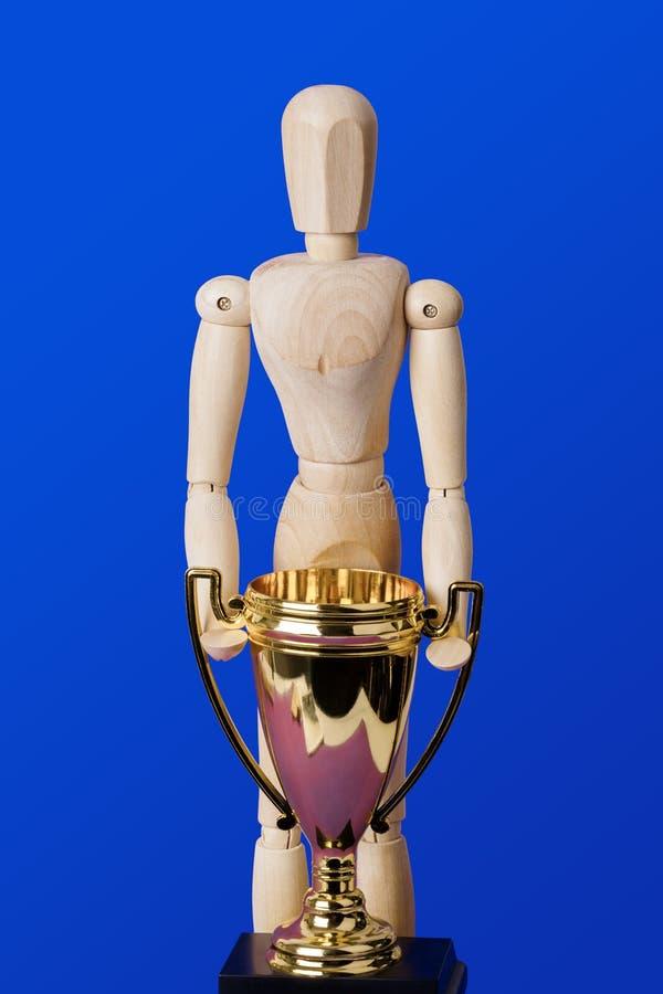 Drewniana zabawkarska postać z złotą trofeum filiżanką na błękicie zdjęcie stock