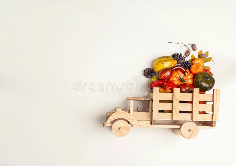 Drewniana zabawki ciężarówka z dyniową uprawą w plecy na beżowym backgr zdjęcia stock