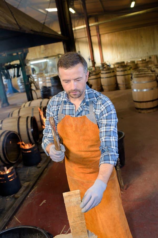 Drewniane baryłki produkcja bednarza używa młot i narzędzia w warsztacie zdjęcie royalty free