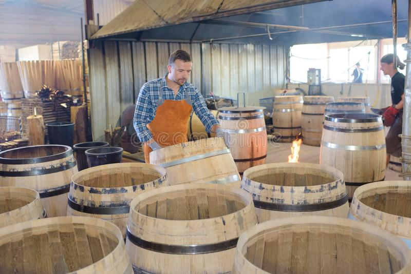 Drewniane baryłki produkcja bednarza używa młot i narzędzia w warsztacie fotografia stock