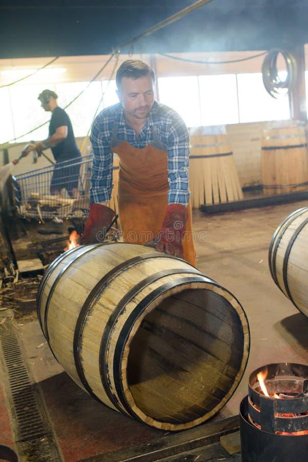 Drewniane baryłki produkcja bednarza używa młot i narzędzia w warsztacie obrazy stock