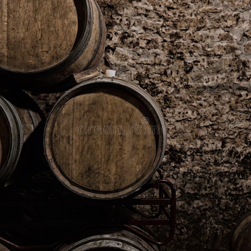 Drewniane baryłki z whisky blisko kamiennej ściany w ciemnym lochu fotografia royalty free