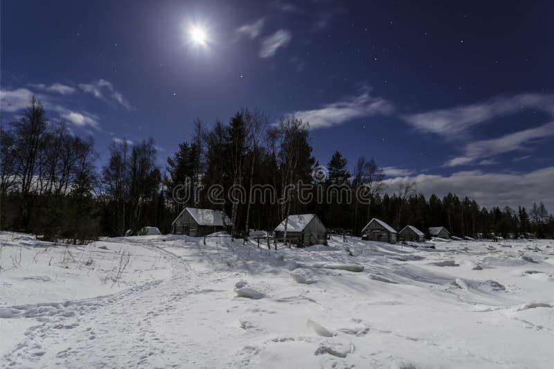 Drewniane budy na brzeg zamarznięta zatoka Biały morze blisko wioski Nilmoguba w moonlit nocy Karelia zdjęcia stock