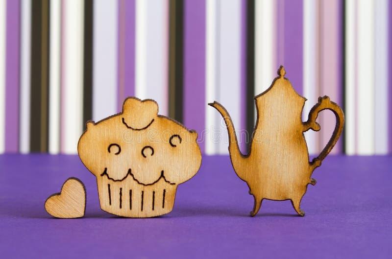 Drewniane ikony tort i teapot z małym sercem na purpurowym stri fotografia stock