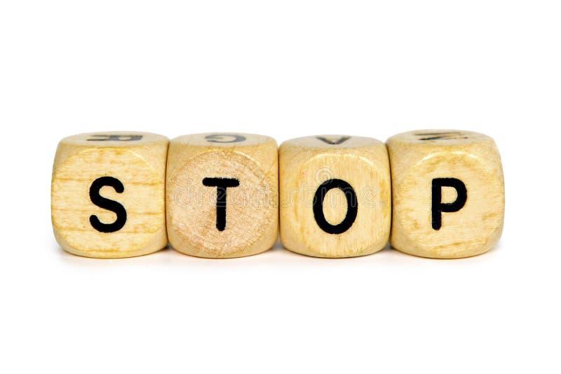 Drewniane listowe kostki do gry tworzy słowo «Zatrzymują «na białym tle zdjęcia royalty free