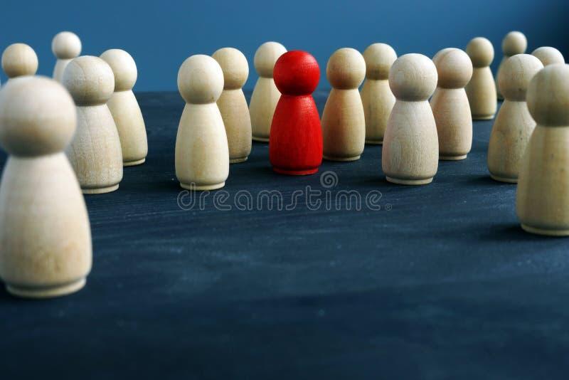 Drewniane postacie i jeden czerwona postać biały różnymi dyskietkami jest tłumy na stanowisko zdjęcia stock