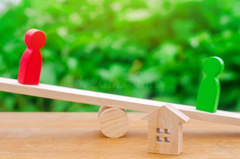 Drewniane postacie na ważą klarowanie posiadanie zdjęcia stock