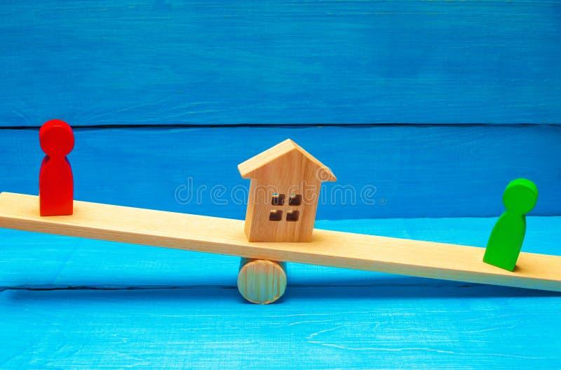 Drewniane postacie na ważą klarowanie posiadanie dom, nieruchomość i własność/ rywale w biznesowej rywalizaci fotografia royalty free
