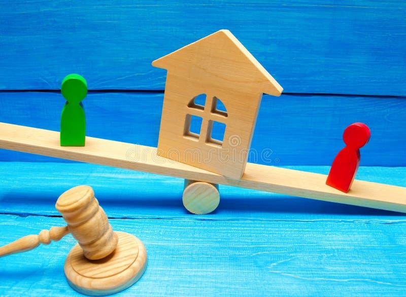 Drewniane postacie na ważą klarowanie posiadanie dom, nieruchomość i własność/ rywale w biznesowej rywalizaci obraz royalty free