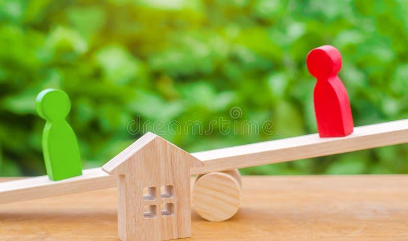Drewniane postacie na ważą klarowanie posiadanie dom, nieruchomość rywale w biznesie rywalizacja, sąd nieruchomości obrazy stock