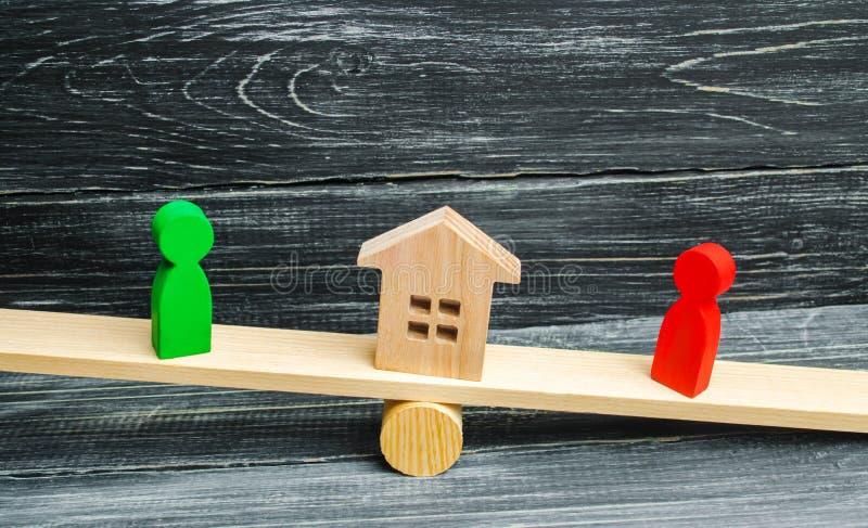 Drewniane postacie na ważą klarowanie posiadanie dom, nieruchomość sąd rywale w biznesie rywalizacja zwycięzca obrazy stock