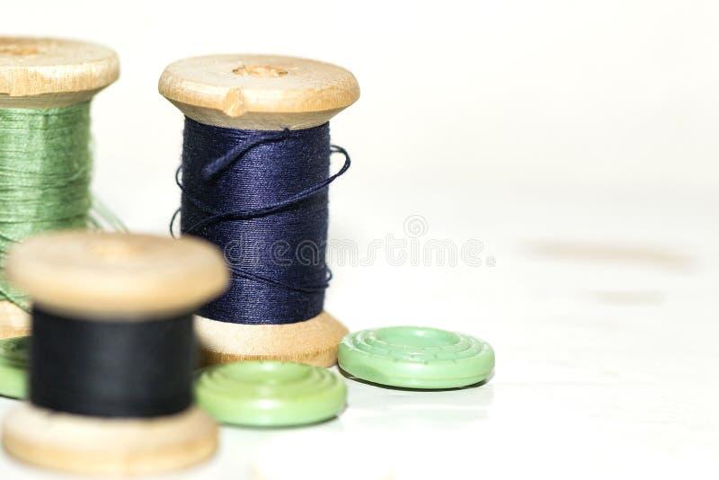 Drewniane zwitki z błękita i zieleni niciami w górę zdjęcia stock