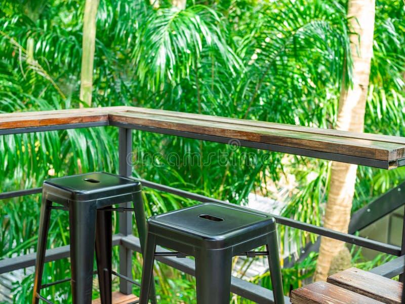 Drewnianego kontuaru prętowi i czarni metali krzesła na tarasie w lasowym tle zdjęcie stock