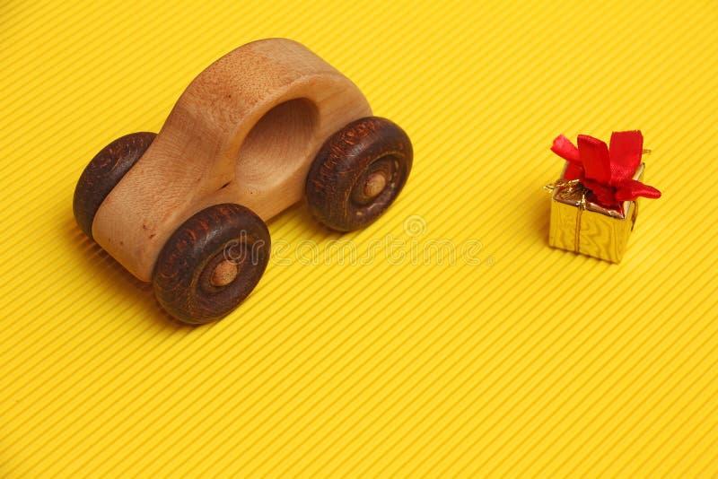 Drewnianego samochodu zabawkarski i złoty prezenta pudełko z czerwonym faborkiem na za panwiowym diagonalnym żółtym tłem, teraźni zdjęcie royalty free