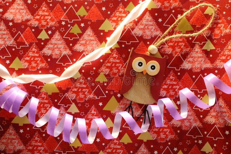 Drewnianej sowy zabawkarski, fiołkowy serpantine z białym faborkiem na świątecznym opakunku jako i fotografia stock