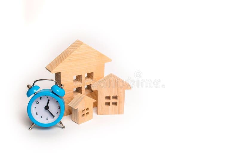 Drewniani domy i błękitny budzik na białym tle Cogodzinny i Chwilowy niedrogi a zdjęcie royalty free