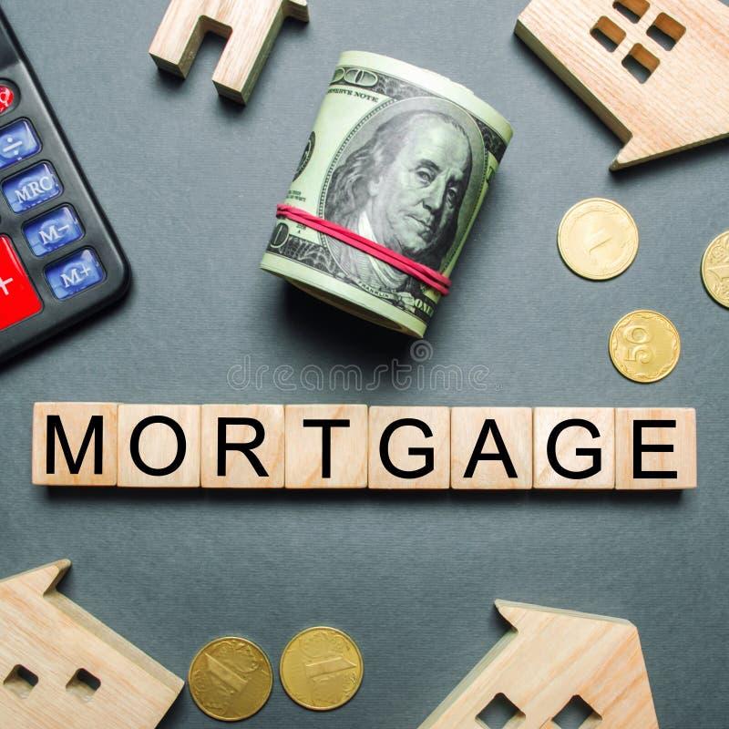 Drewniani domy, kalkulator, wpisuj?, monety i bloki z s?owo hipotek? Kupowa? dom w d?ugu Nabywa dom na kredycie obraz stock