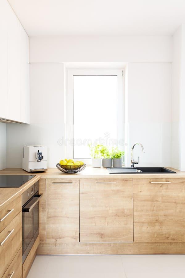 Drewniani gabinety w jaskrawym minimalnym białym kuchennym wnętrzu z wi obraz royalty free