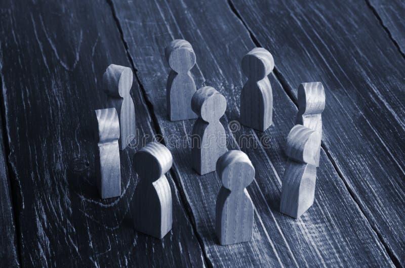 Drewniani kędzierzawi ludzie stojaka w okręgu wokoło osoby na dar fotografia royalty free